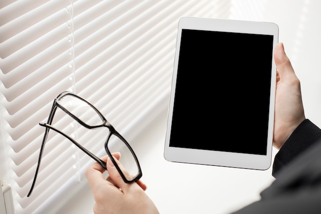 Close-up com as mãos segurando o tablet Foto gratuita