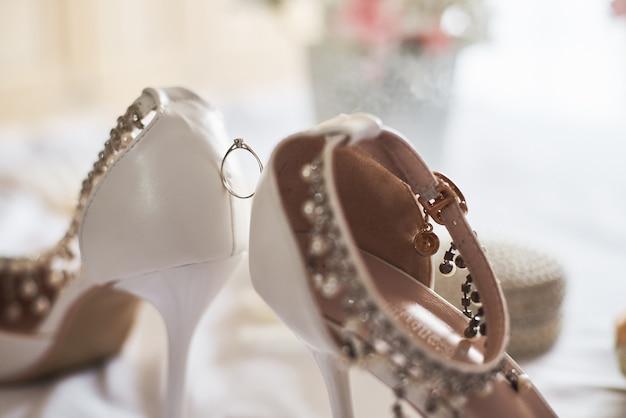 Close-up da aliança de casamento entre as sapatas nupciais brancas. Foto Premium