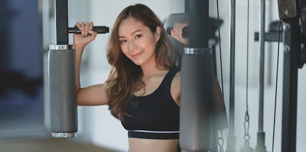 Close-up da bela mulher asiática com corpo bronzeado e magro exercício na máquina Foto Premium