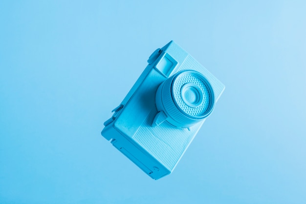 Close-up da câmera pintada no ar contra o pano de fundo azul Foto gratuita