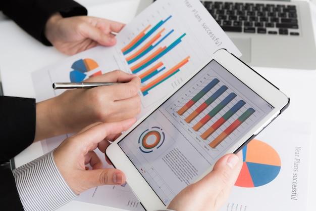Close-up da equipe do negócio que usa a tabuleta digital com d financeira Foto gratuita