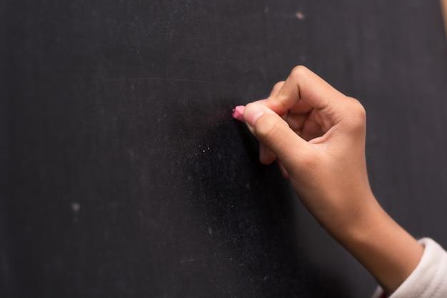 Close-up da escrita da mão direita em um quadro negro Foto gratuita