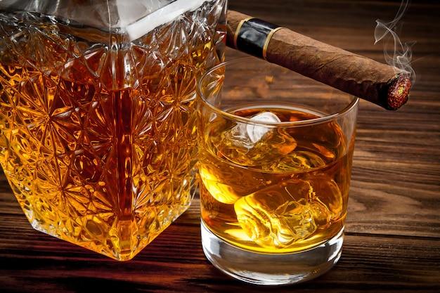 Close up da garrafa, copo com uísque e fumar charuto Foto Premium