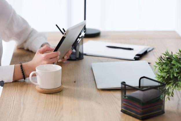 Close-up da jovem empresária usando tablet digital com uma xícara de café; laptop na mesa de madeira Foto gratuita