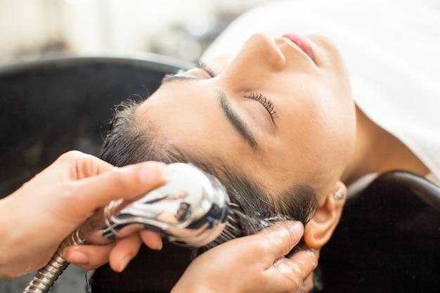 Close-up da jovem mulher relaxada no salão de cabeleireiro Foto gratuita