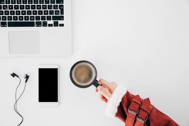 Close-up da mão da fêmea segurando a xícara de café sobre a mesa de escritório com laptop; telefone celular e fone de ouvido Foto gratuita