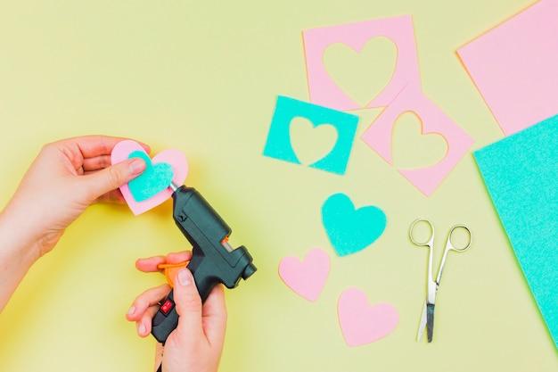 Close-up da mão da mulher, furando a forma de coração de papel com pistola de cola quente elétrico Foto gratuita