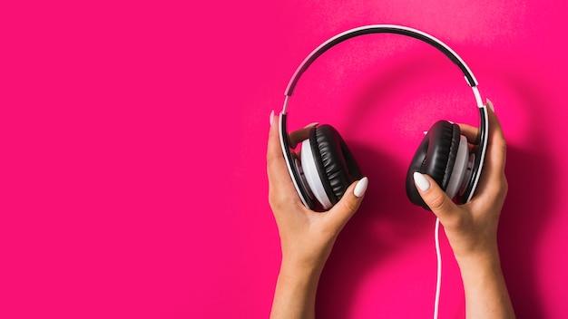 Close-up da mão da mulher segurando o fone de ouvido no fundo rosa Foto gratuita