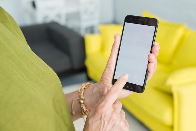 Close-up da mão da mulher sênior tocando a tela do celular Foto gratuita