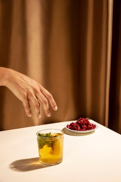 Close-up da mão da pessoa sobre o copo de coquetel caseiro perto de sementes de romã na mesa Foto gratuita
