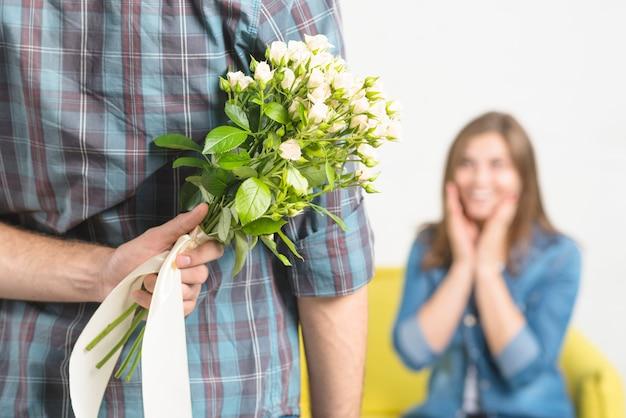 Close-up da mão de um homem escondendo flores de sua namorada Foto gratuita