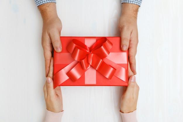 Close up da mão de um homem que dá uma caixa vermelha com um presente a uma mulher. Foto Premium