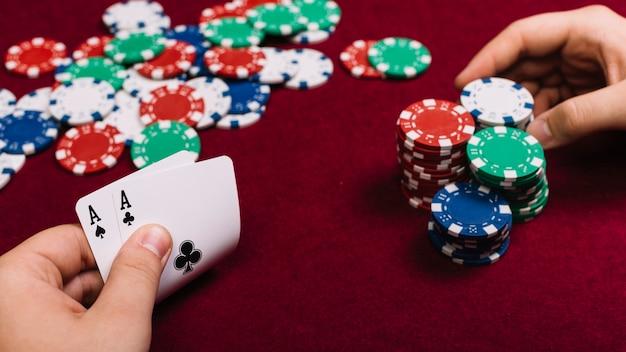 Close-up da mão de um jogador de poker com cartas e fichas Foto gratuita