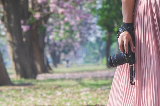 Close-up da mão de uma mulher segurando a câmera. Foto Premium