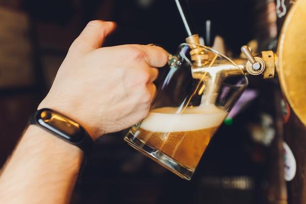 Close-up da mão do empregado de bar na torneira de cerveja, derramando uma cerveja de pressão. Foto Premium
