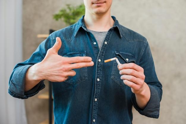 Close-up da mão do homem, mostrando o gesto de arma perto do cigarro quebrado Foto gratuita