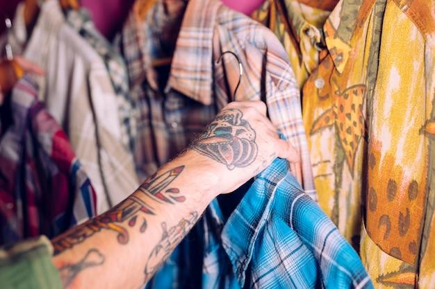 Close-up da mão do homem segurando a camisa azul no trilho na loja de roupas Foto gratuita