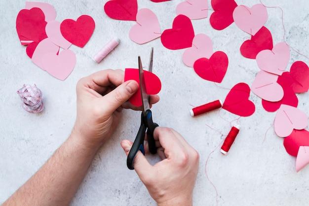 Close-up da mão do homem, tornando a guirlanda de forma de coração no pano de fundo texturizado branco Foto gratuita