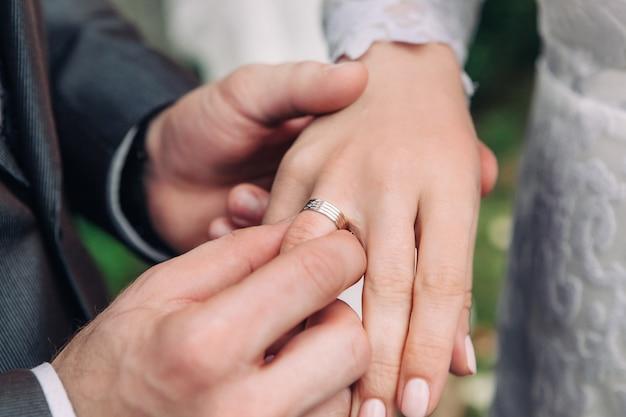 Close-up da mão do noivo coloca um anel de casamento no dedo noivas, a cerimônia na rua, foco seletivo Foto Premium
