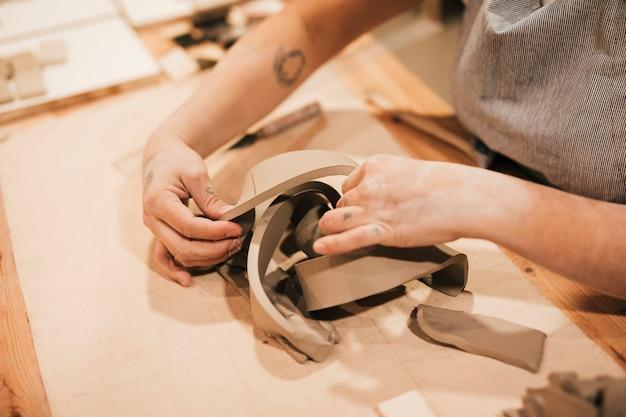 Close-up da mão do oleiro feminino trabalhando a argila na superfície da mesa Foto gratuita