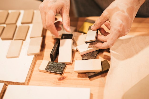 Close-up da mão do oleiro feminino trabalhando com telhas cerâmicas na mesa Foto gratuita