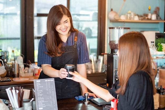 Close up da mão feminina está tomando café quente de barista Foto Premium