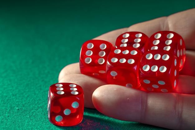 Close up da mão que guarda dados vermelhos com uma combinação de vencimento no pano verde em um casino. Foto Premium