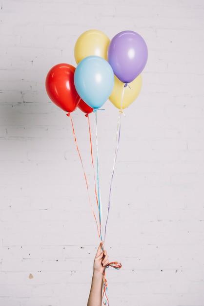 Close-up da mão segurando balões coloridos na mão contra a parede branca Foto Premium