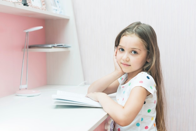 Close-up da menina bonitinha estudando Foto gratuita
