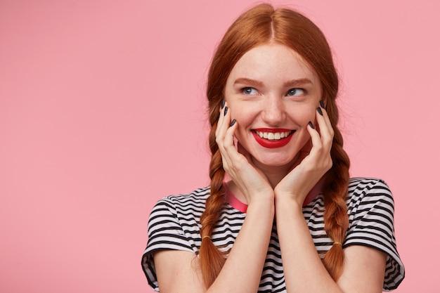 Close-up da misteriosa encantadora garota ruiva bonita com duas tranças mantém as mãos perto do rosto e sorrindo animadamente com lábios vermelhos, olhando para o lado esquerdo no espaço da cópia, isolado Foto gratuita