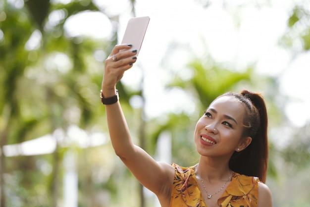 Close-up da mulher asiática elegante feliz com rabo de cavalo e maquiagem tomando selfie com smartphone Foto gratuita