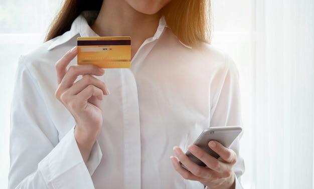 Close up da mulher feliz em usar cartão de crédito e smartphone para pagar a compra on-line Foto Premium