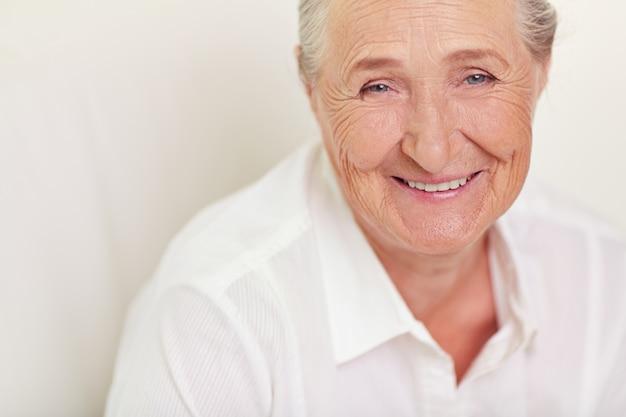 Close-up da mulher idosa com camisa branca Foto gratuita