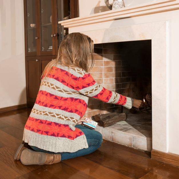 Close-up da mulher queimando fogo na lareira em casa Foto gratuita