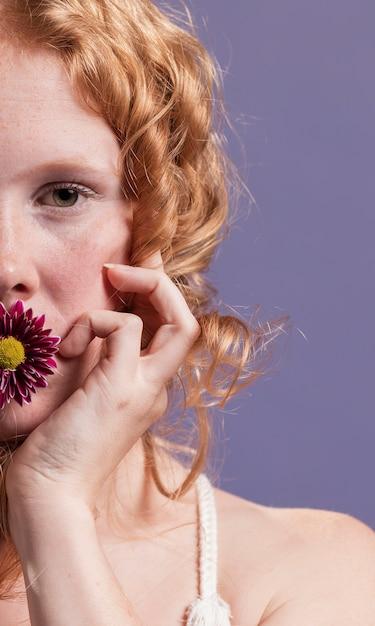 Close-up da mulher ruiva posando com uma flor na boca dela Foto gratuita