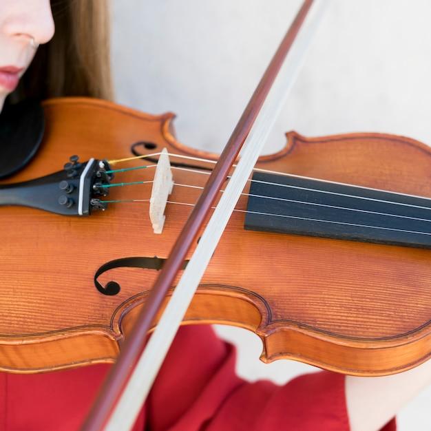 Close-up da mulher tocando violino Foto gratuita
