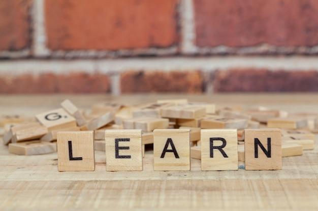 Close up da palavra aprender no bloco de madeira Foto Premium