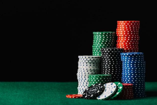 Close-up da pilha de fichas de casino na mesa de poker verde Foto gratuita
