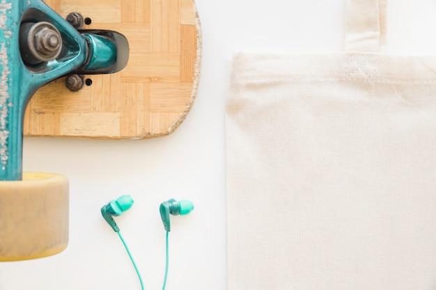Close-up da roda de skate, fone de ouvido e saco de algodão no fundo branco Foto gratuita