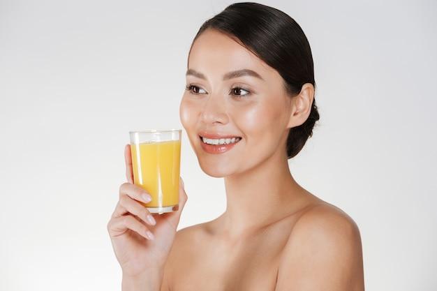 Close-up da senhora seminua com pele fresca saudável e sorriso amplo, bebendo suco de laranja de vidro transparente, isolado sobre a parede branca Foto gratuita