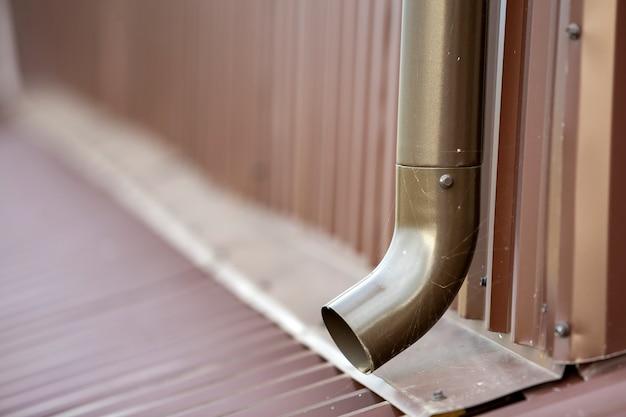 Close-up da tubulação nova marrom do sistema do metal da calha na parede. proteção de drenagem, trabalho profissional. Foto Premium