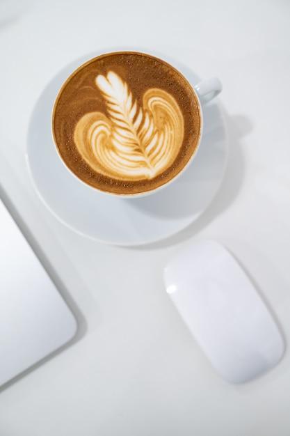 Close-up da xícara de café latte art com mouse e computador portátil plana leigos Foto Premium