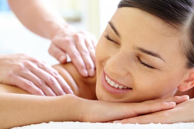 Close-up das mãos do massagista massagens para trás de um cliente Foto gratuita