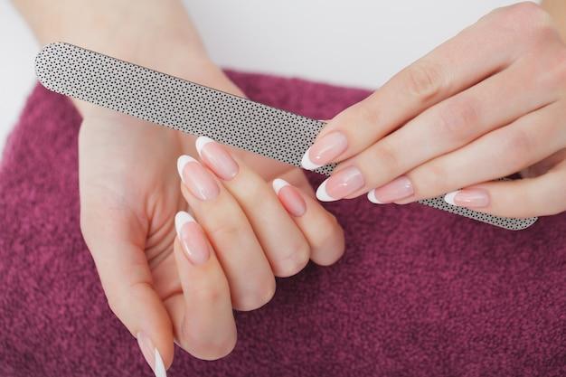 Close up das mãos fêmeas bonitas que têm o tratamento de mãos dos termas no salão de beleza. pregos naturais saudáveis de filing clients do esteticista com arquivo de prego. Foto Premium
