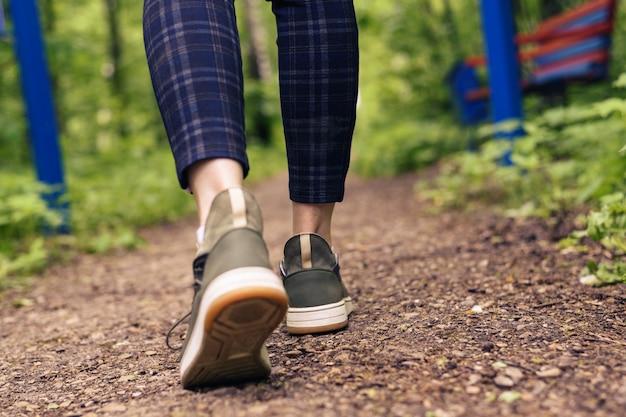 Close-up das pernas das mulheres de tênis verdes e calças em uma gaiola ir em uma estrada da floresta. hls, ande ao ar livre Foto Premium
