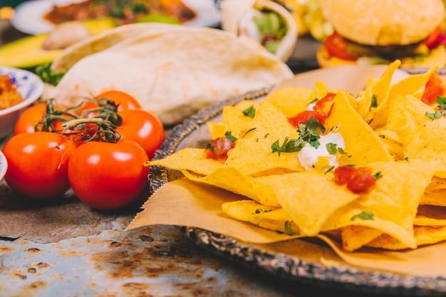 Close-up, de, amarela, mexicano, nacho, lascas, com, tomate cereja Foto gratuita