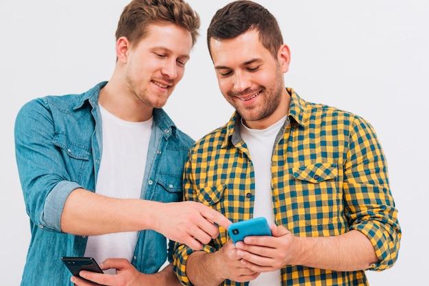 Close-up, de, amigo masculino, mostrando, algo, ligado, telefone móvel Foto gratuita