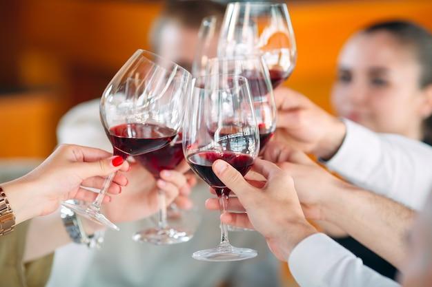 Close-up de amigos brindando copos de vinho na festa Foto Premium
