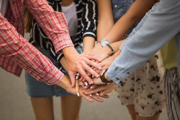 Close-up, de, amigos, pôr, mãos, cima, um ao outro Foto gratuita