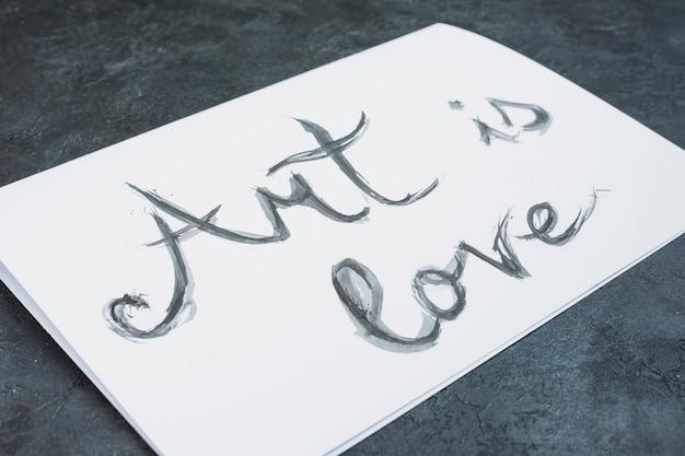 Close-up de aquarela mão desenhada 'arte é amor' texto em papel branco Foto gratuita